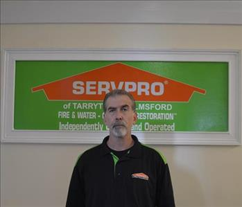 Male Employee in black shirt in front of SERVPRO logo