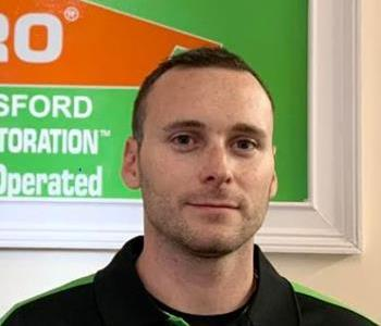 Male Employee in Black Shirt with green stripe smiling in front of SERVPRO green sign.
