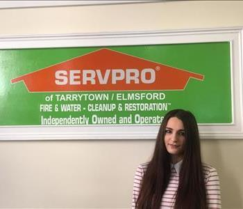 Female Employee with dark hair in front of SERVPRO logo
