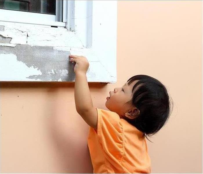 Toddler with orange shirt peeling off paint off a window sill
