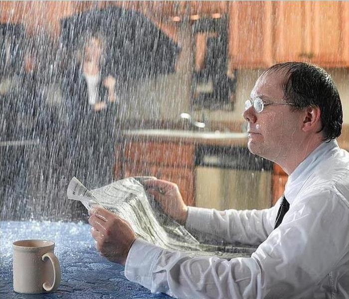 Man sitting reading newspaper while it is raining in the dining room